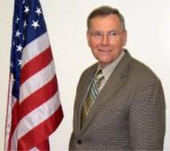 Photo of Bob Farischon standing next to American flag
