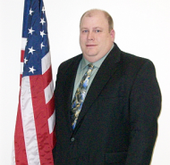 Photo of Eric Scheid standing next to American flag